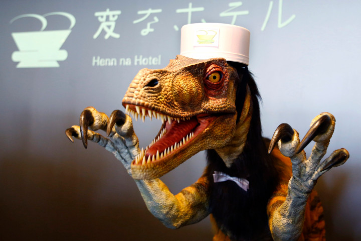 """A receptionist dinosaur robot performs at the new robot hotel, aptly called Henn na Hotel or Weird Hotel, in Sasebo, southwestern Japan, Wednesday, July 15, 2015. From the receptionist that does the check-in and check-out to the porter that's a stand-on-wheels taking luggage up to the room, the hotel, that is run as part of Huis Ten Bosch amusement park, is """"manned"""" almost totally by robots to save labor costs. (AP Photo/Shizuo Kambayashi)"""