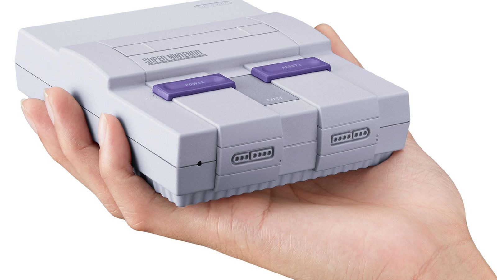 a nintendo snes classic being held against a white background