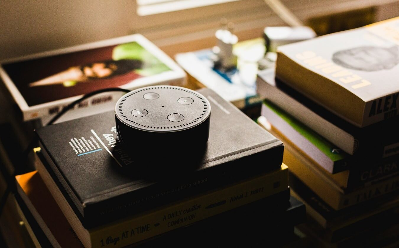 amazon echo sitting on a stack of books