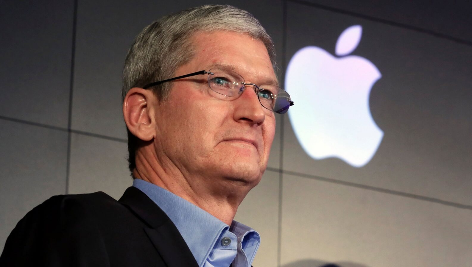 apple's tim cook standing with an apple logo behind him