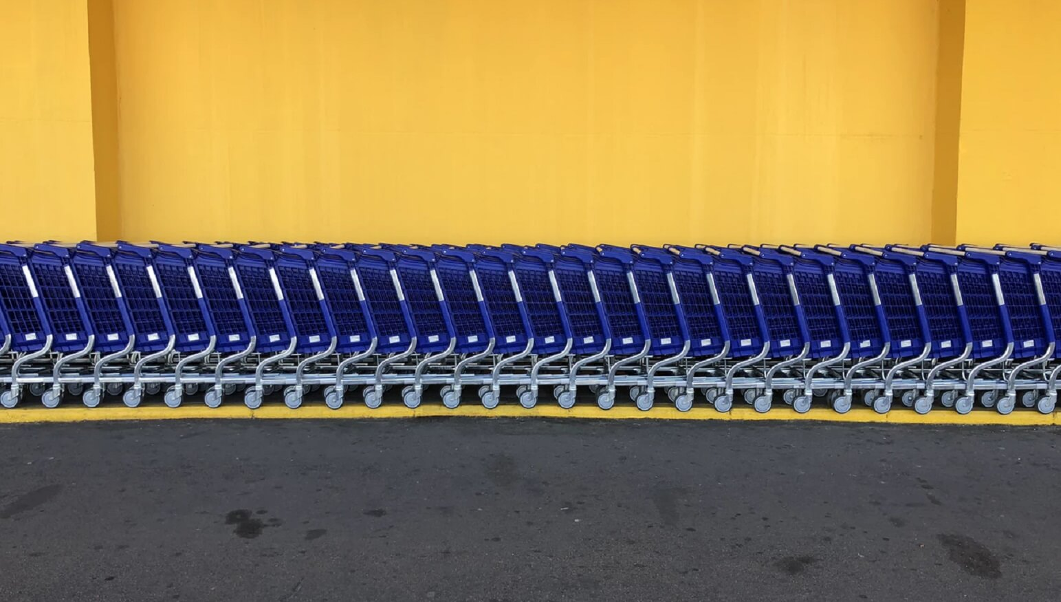 walmart shopping carts against yellow wall