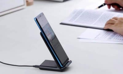 anker charging stand on a desk near writing papers