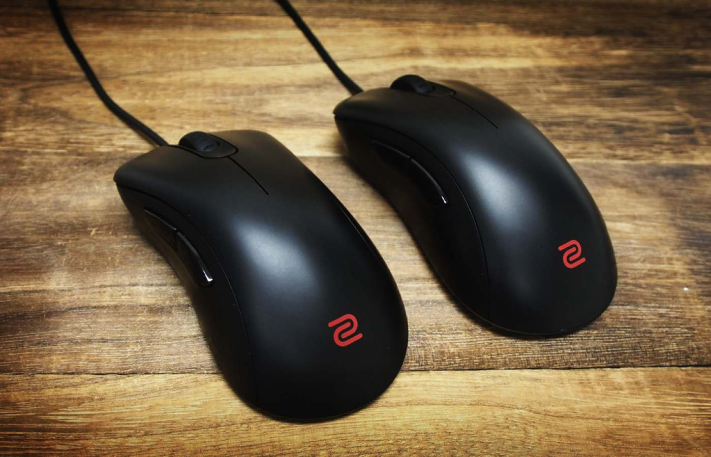 two benq zowie gaming mouses on a hardwood floor
