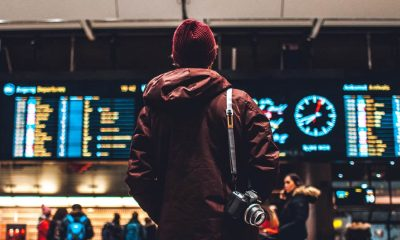 man standing at airport looking at travel directions