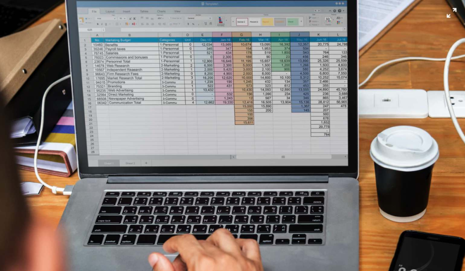 laptop with microsoft excel open on a desk with cup of coffee