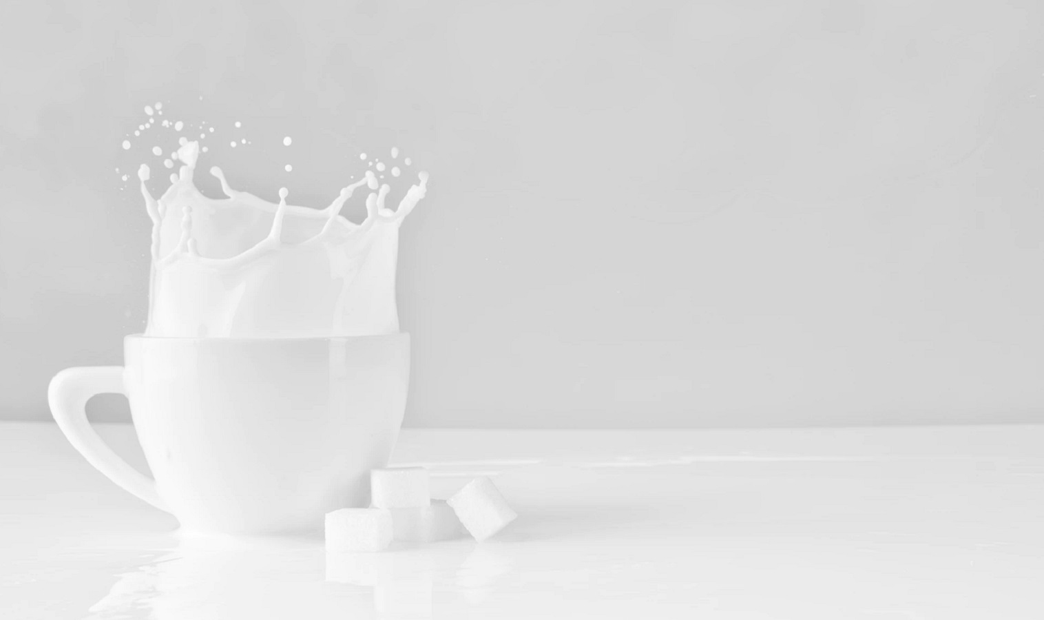 milk splashing out of a pitcher on a table