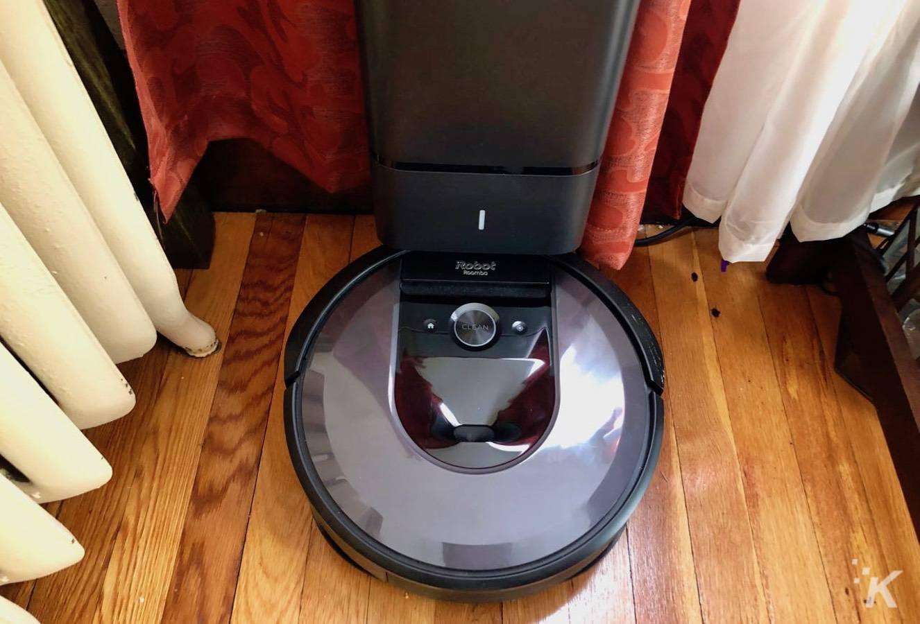 irobot roomba i7+ sitting on charger clean base hardwood floors