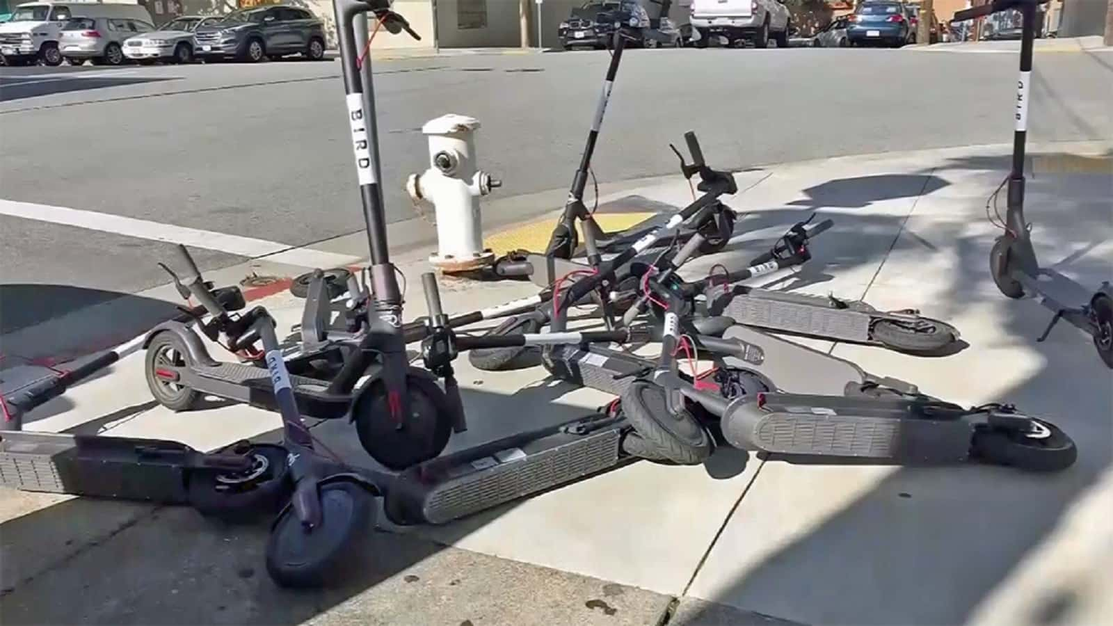 scooter and bird electric scooters thrown on ground
