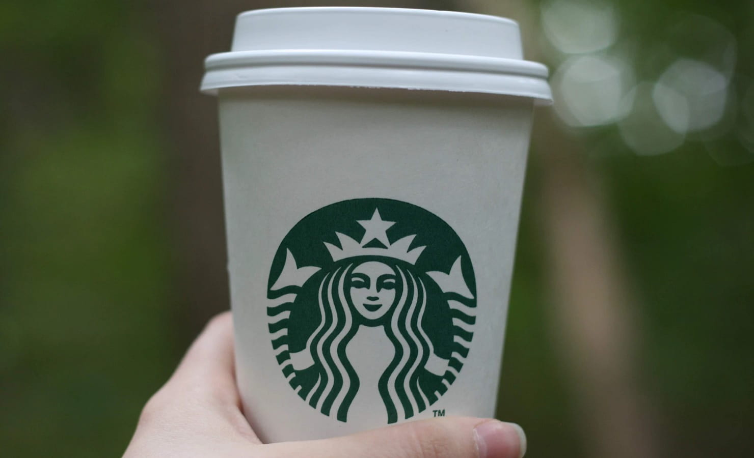 person holding a white starbucks cup
