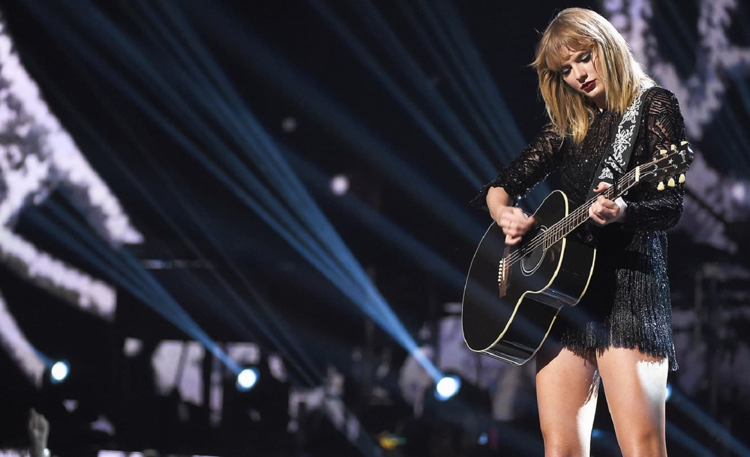 taylor swift playing guitar at concert