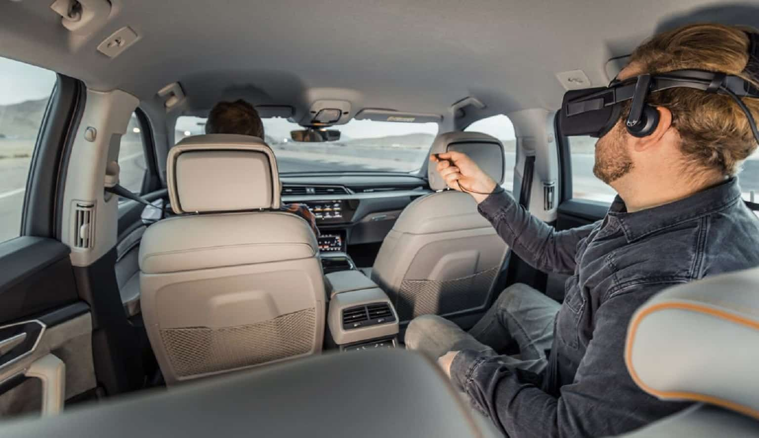 audi vr experience with person in the back seat wearing vr goggles