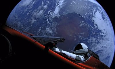 tesla in space with earth in background