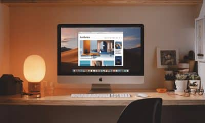 imac setting on table surrounded by other desk items and lamp
