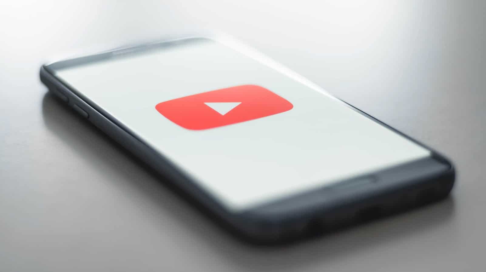 youtube logo on a phone sitting on a desk