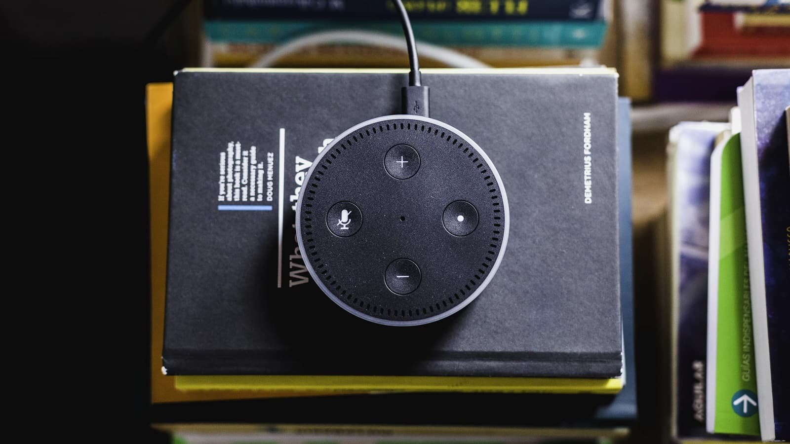 amazon echo speaker on a stack of books