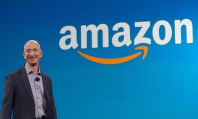 amazon logo behind a standing jeff bezos
