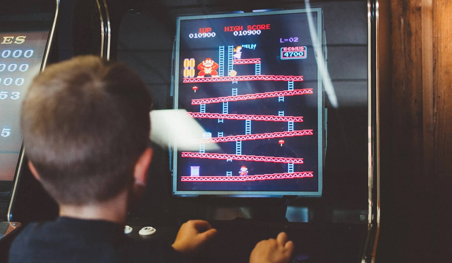 kid playing donkey kong arcade game
