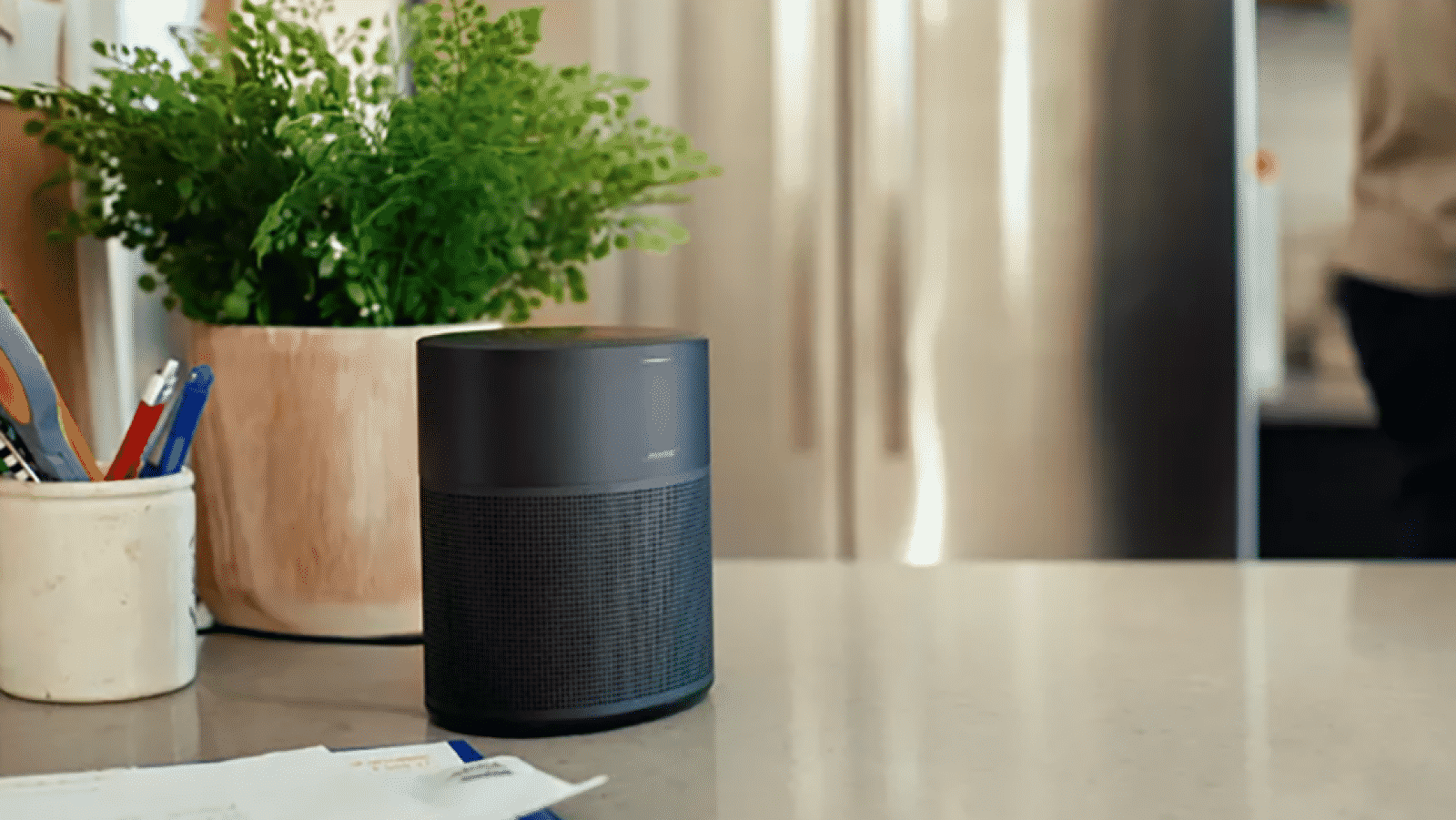 bose home 300 smart speaker on countertop with plants and letters