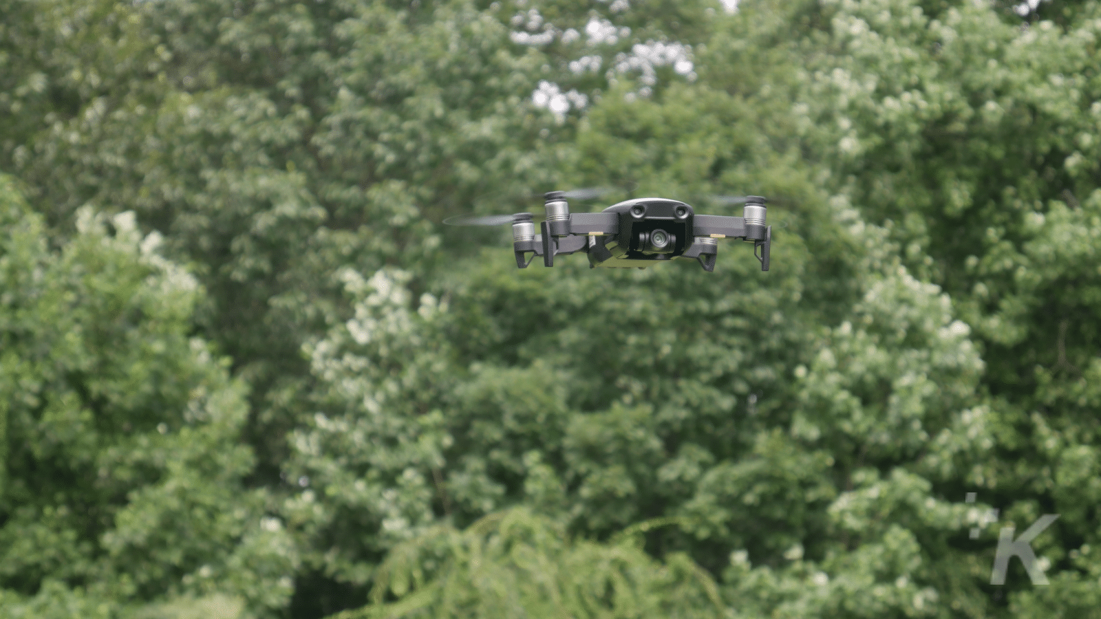 dji mavic air in flight in front of trees