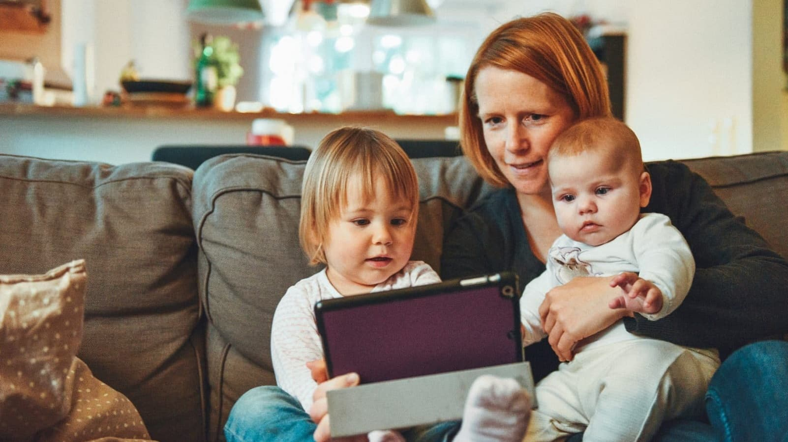 mother looking at a tablet with her children