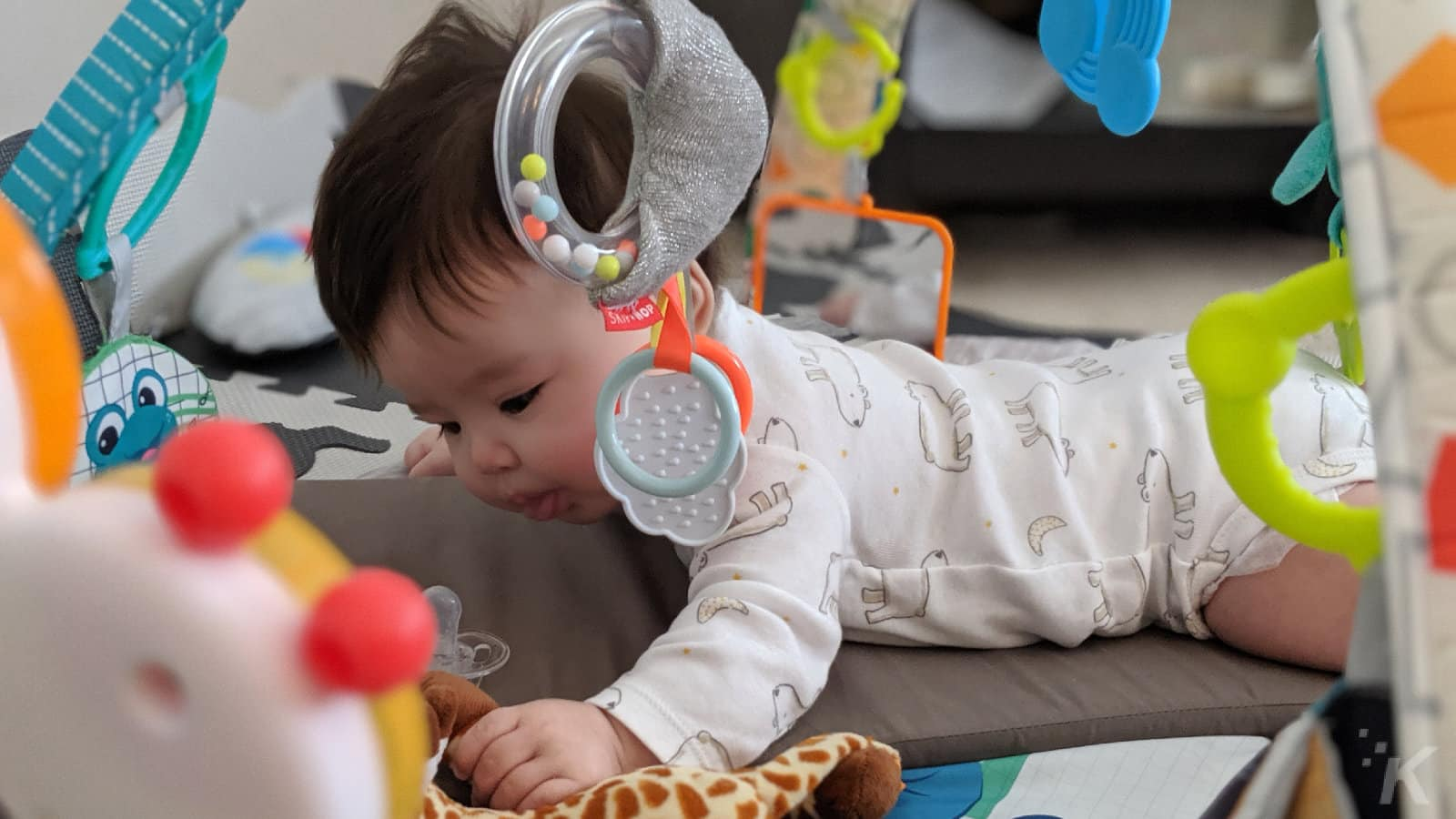 baby intently playing with toys on tranquilo mat