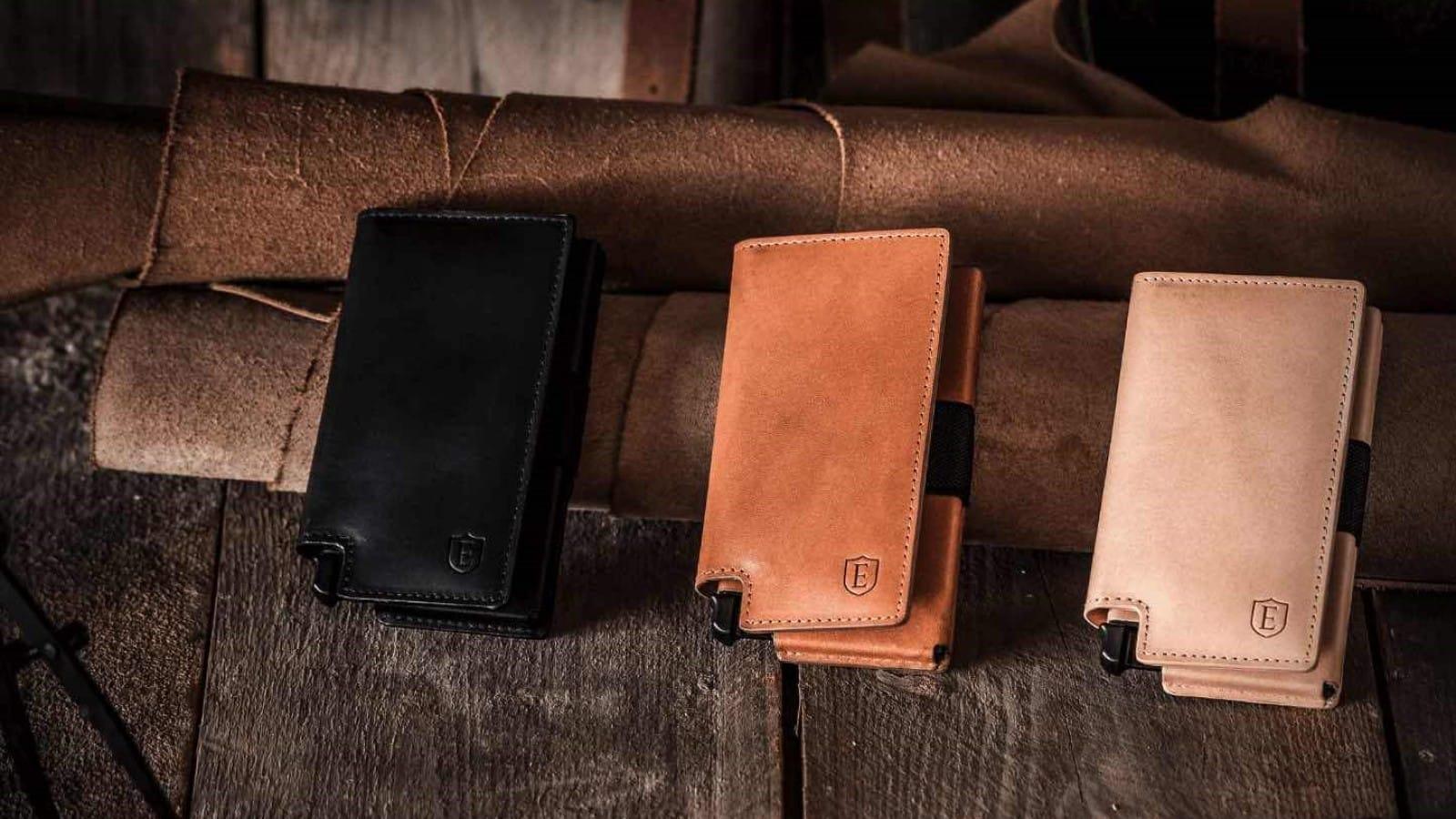 three ekster slim wallets on wooden backdrop