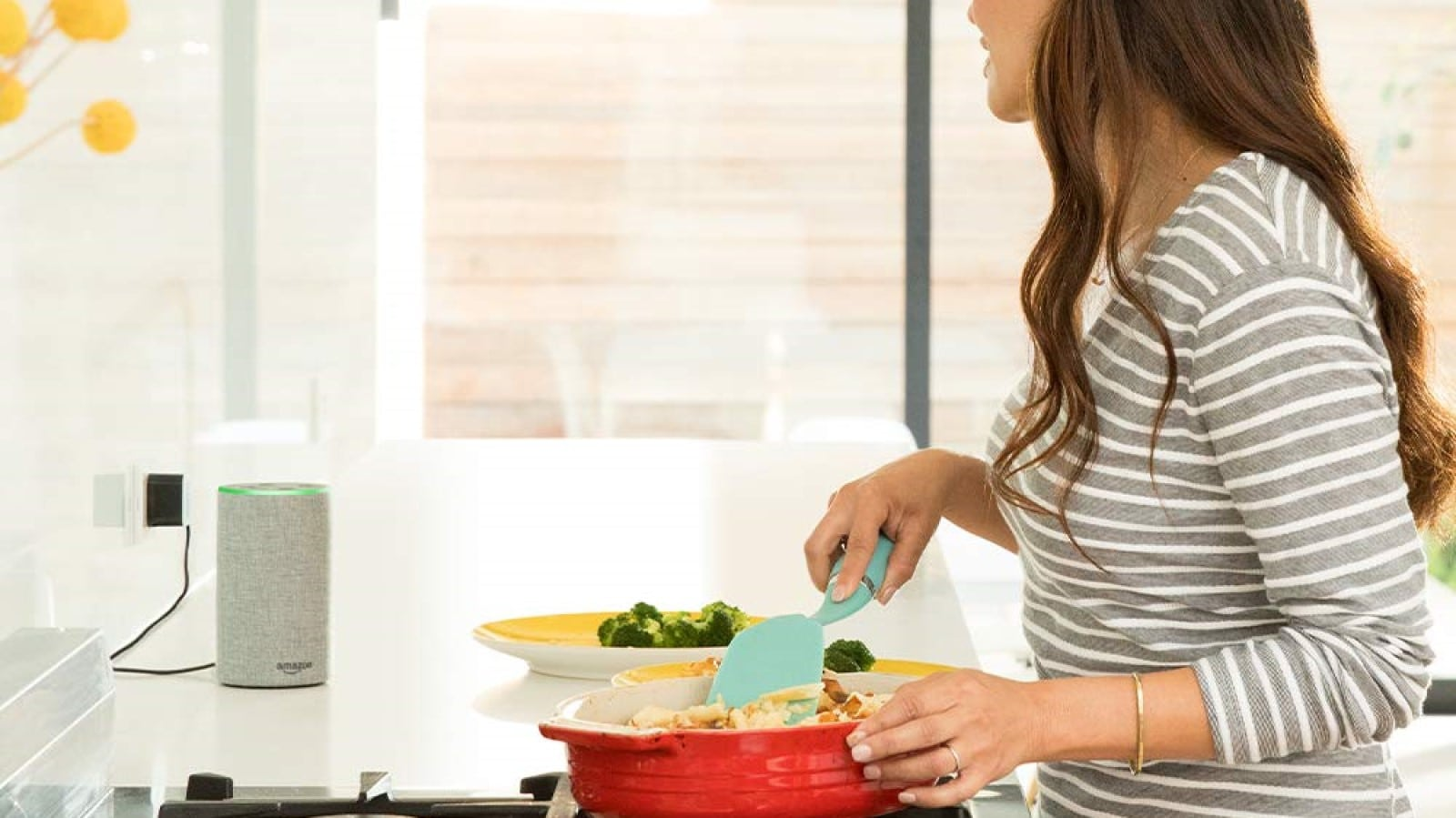 amazon echo smart speaker on kitchen counter while woman cooks a meal on stove