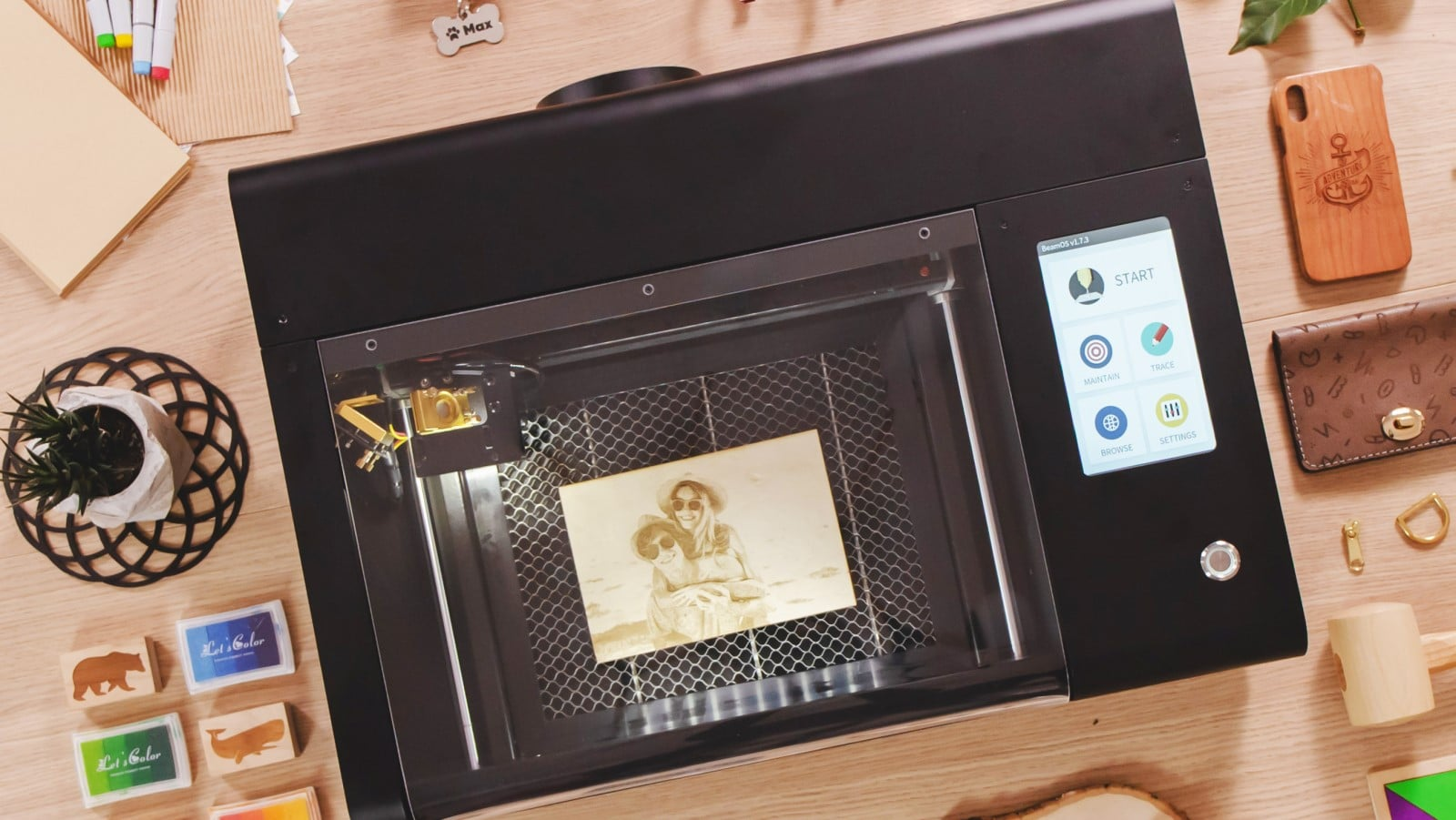 beamo laser cutter surrounded by things created on it
