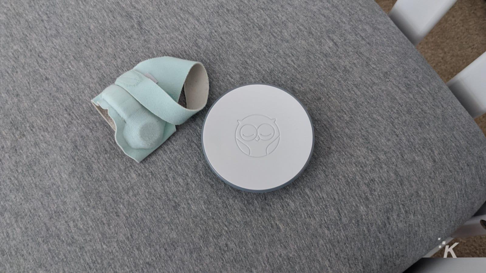 owlet smart sock and base unit on a crib mattress
