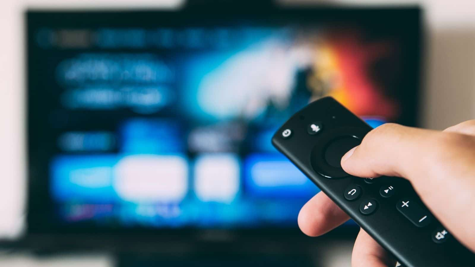 someone using a remote on the tv for torrents