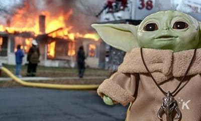 baby yoda standing in front of a house fire