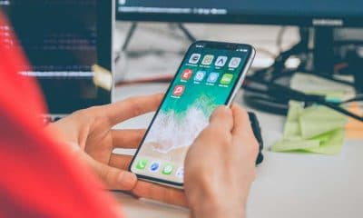 person holding iphone at desk