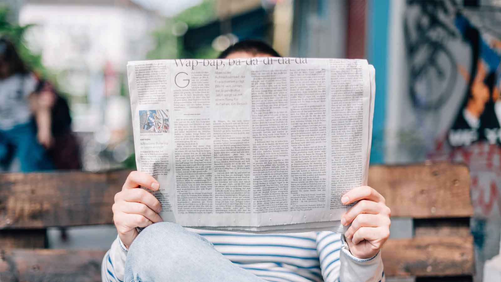 person reading local newspaper