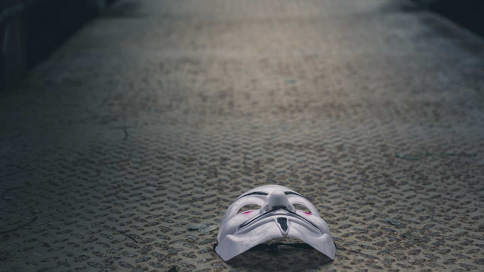 a guy fakes mask on the floor of a footbridge