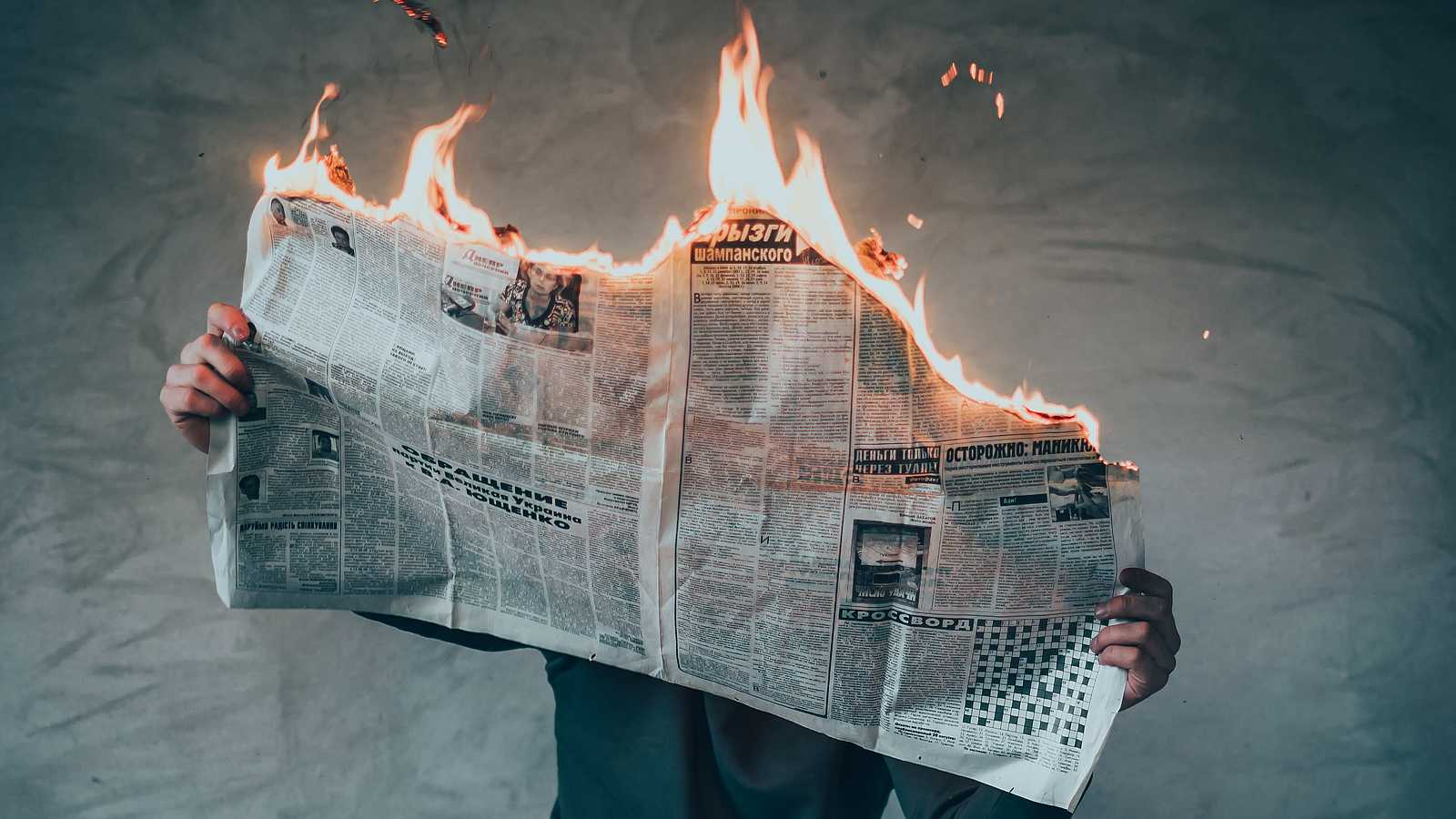 person reading a burning newspaper