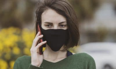 person wearing covid-19 mask and talking on smartphone
