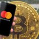 mastercard on smartphone with cryptocurrency behind it