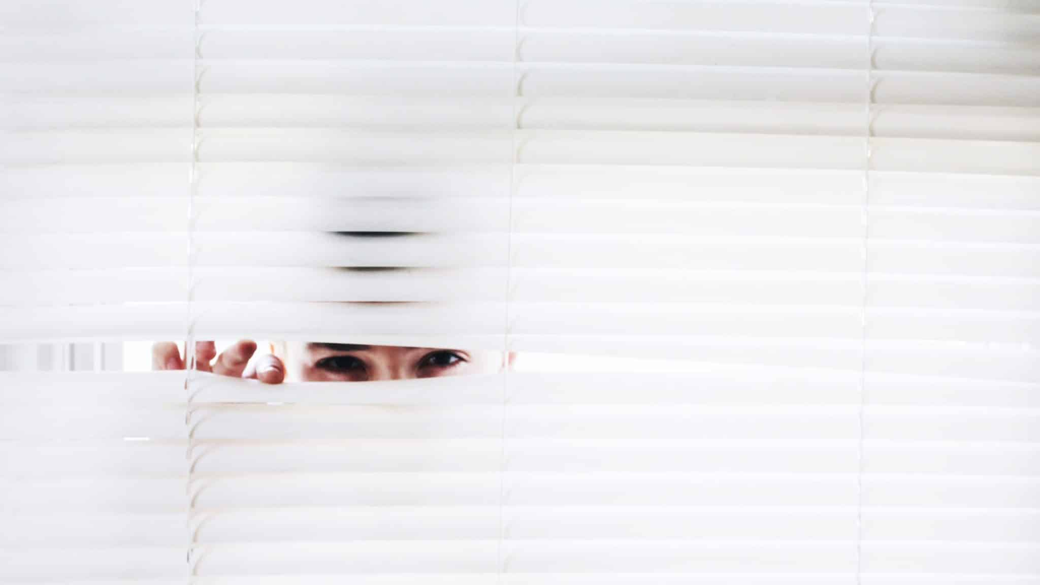 person looking through blinds