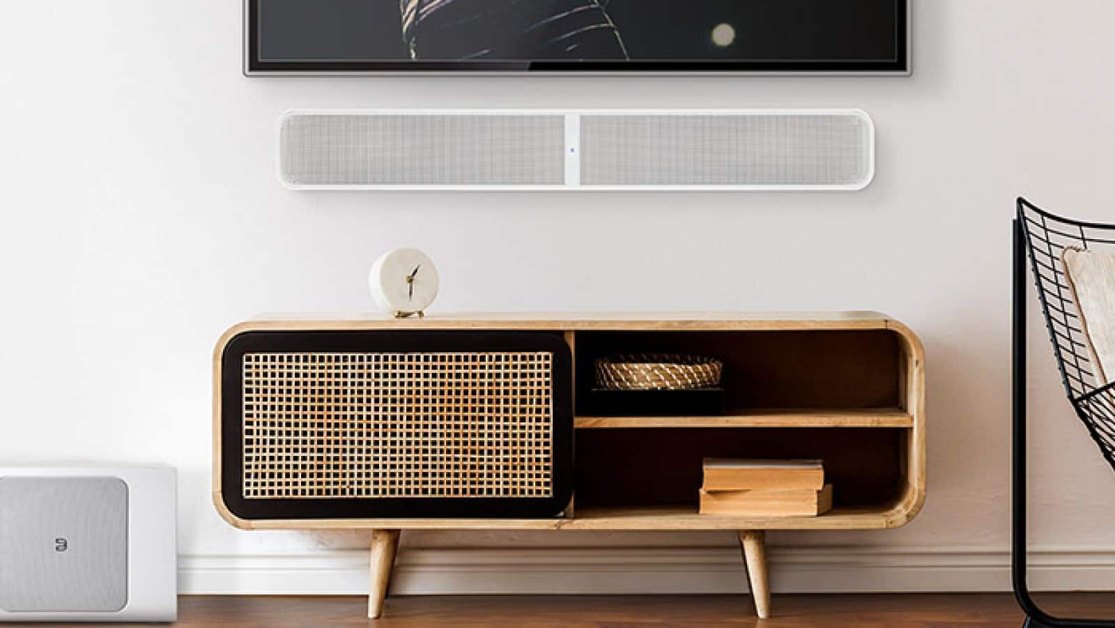 bluesound pulse soundbar plus mounted on wall between a TV and the floor