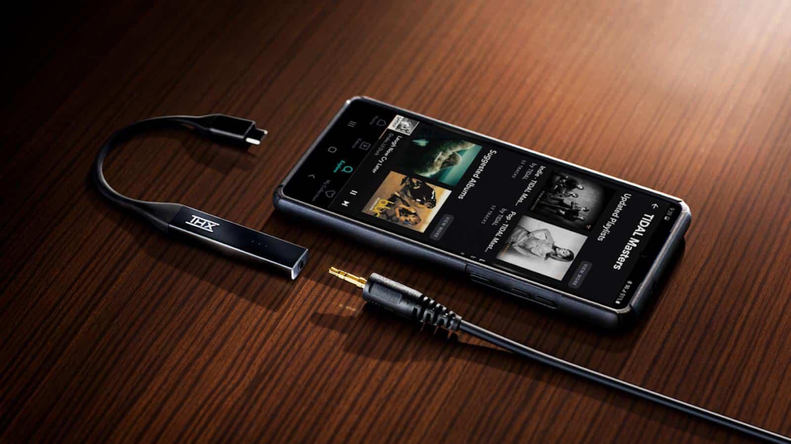 thx onyx dac amp on table next to smartphone and headphone plug