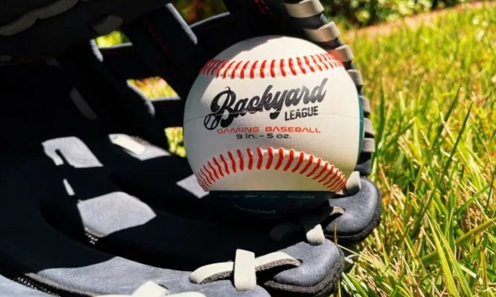 backyard league smart connected baseball resting inside a baseball glove that's laying on the grass