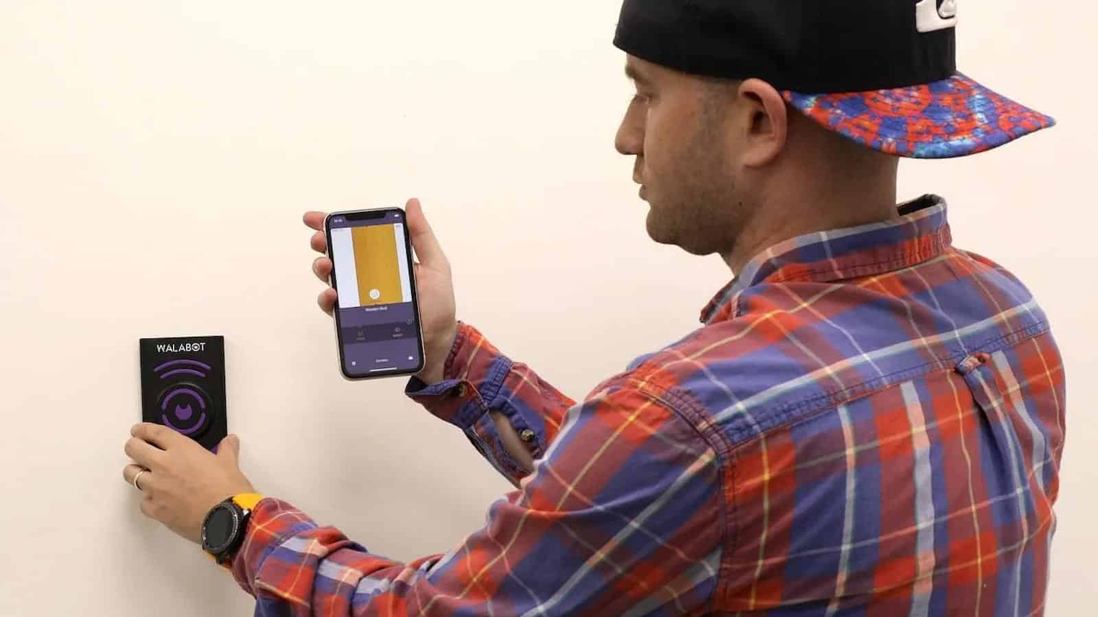 walabot diy 2 stud finder being used by a man in a baseball cap to find pipes inside a wall